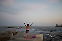 Spain - Barcelona - A young man performing the sun salutation at sunset facing the Mediterranean sea.