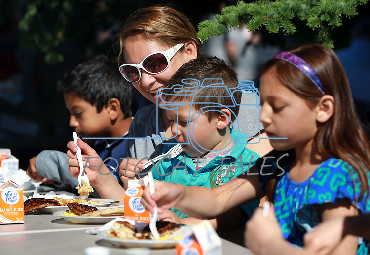 Angie Navarete and her children, from left, Diego Cortez, 11, Kaelan Cortez, 3, and Karely Cortez, 9, enjoy the Carson City Library Summer Reading Program Pancake Breakfast Kick-Off on Saturday morning. The event also included a big book sale, face painting and reading program sign-ups..Photo by Cathleen Allison/Nevada Photo Source