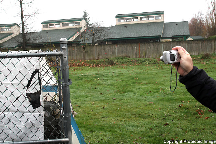King County Animal Care and Control cruelty investigator, Sgt. David Morris, takes a picture of a muzzle hanging on a fence where a dog is tethered in Enumclaw, Wash. on December 10, 2008.  The Husky mix had no water, was living admist feces everywhere, and his shelter was too small for him. (Karen Ducey/Seattle Post-Intelligencer)
