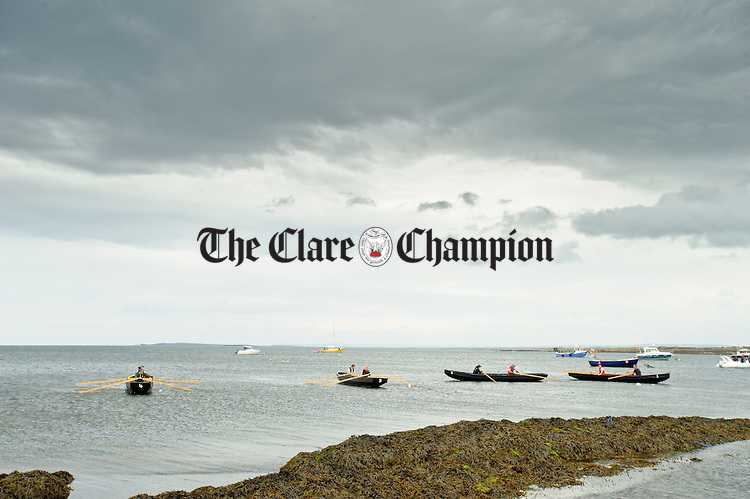 The boats line up at the start for a race during the All-Ireland  Currach Regatta at Doonbeg. Photograph by John Kelly.