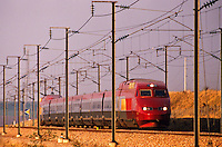 France. Thalys, high speed train, running through cable supports and pylons. Evening.  Express train between Paris, Brussels and Amsterdam.