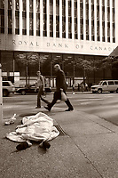 Pedestrians walk beside a homeless woman sleeping on the sidewalk facing  the Royal Bank of Canada building on King Street West in downtown Toronto, April 20, 2007.<br />