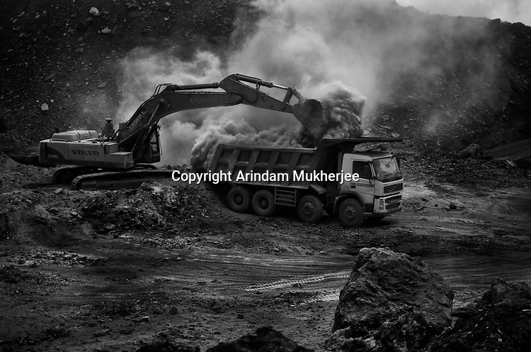 A truck is loaded with debris to cover the fissures on the ground. A huge coal mine fire is engulfing the city of Jharia from all its sides. All scientific efforts have gone in vain to stop this raging fire. This fire is affecting lives of people living in and around Jharia. Jharkhand, India. Arindam Mukherjee