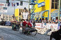 Rick Casillo and team leave the ceremonial start line with an Iditarider at 4th Avenue and D street in downtown Anchorage, Alaska during the 2015 Iditarod race. Photo by Jim Kohl/IditarodPhotos.com