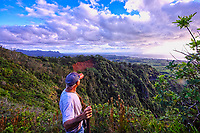 Shortly after sunrise, a hiker looks out at the Coconut Coast on the east shore of Kaua'i.