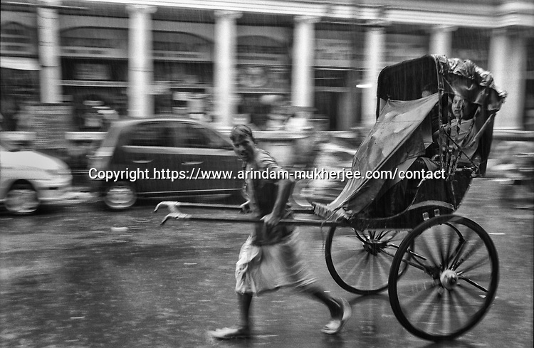 A rickshaw puller carries passenger under a heavy rain in Kolkata, India.