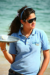 Cabo San Lucas waitress holds a tray containing two cups of whiskey.