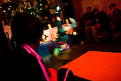 """A young Bhutanese boy swings to Latino tracks while other young men gather in large numbers in bars similar to this one in the New Lee Drayang and Throkhang in Thimphu, Bhutan. Television and the internet have been accessible only since 1999 in Bhutan, and were introduced despite widespread fears that their """"controversial"""" content such as fashion shows, western music, wrestling, and pornography, could destroy the kingdom's traditional way of life based on unique Buddhist principles. The Bhutanese people elected the remote Himalayan nation's first democratic government when it voted for a National Assembly on March 24, 2008, in a landmark vote proposed by the royal family to peacefully transform the small Buddhist kingdom into a constitutional monarchy. Photo: Sanjit Das/Panos"""