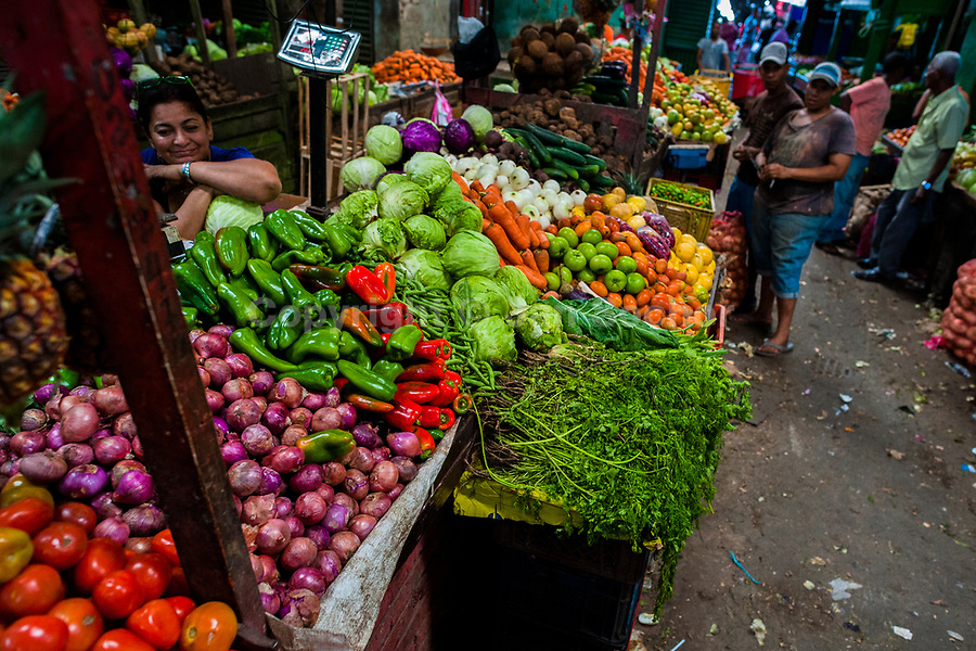 Piles of vegetables and tropical fruits are seen arranged on the stands in the market of Bazurto in Cartagena, Colombia, 14 December 2017. Far from the touristy places in the walled city, a colorful, vibrant labyrinth of Cartagena's biggest open-air market sprawls to the Caribbean seashore. Here, in the dark and narrow alleys, full of scrappy stalls selling fruit, vegetables and herbs, meat and raw fish, with smelly garbage on the floor and loud reggaeton music in the air, the African roots of Colombia are manifested.