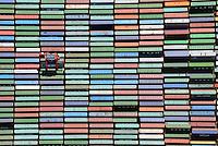 Container und Carrier am Burchardkaii: EUROPA, DEUTSCHLAND, HAMBURG, (EUROPE, GERMANY), 29.06.2014 Der HHLA Container Terminal Burchardkai ist die groesste und aelteste Anlage für den Containerumschlag im Hamburger Hafen. Hier, wo 1968 die ersten Stahlboxen abgefertigt wurden, wird heute etwa jeder dritte Container des Hamburger Hafens umgeschlagen. 25 Containerbruecken arbeiten an den Tausenden Schiffen, die hier jaehrlich festmachen, und taeglich werden mehrere Hundert Eisenbahnwaggons be- und entladen. Mit dem laufenden Aus- und Modernisierungsprogramm wird die Kapazität des Terminals in den kommenden Jahren schrittweise ausgebaut. <br /> Der wichtigste und bekannteste Containertyp ist der 40 feet Container fuer die Handelsschifffahrt mit den Maßen 12,192 × 2,438 × 2,591 m. Von diesem Containertyp nach ISO 668 (freight container) sind ueber Millionen im Verkehr.<br /> Der Fracht- oder Schiffscontainer wurde im Jahr 1956 von dem Reeder Malcolm McLean an der US-Ostkueste fuer den Gueterverkehr eingefuehrt.  Die Frachtcontainer wurden zur Basis der Globalisierung der Wirtschaft; mit ihnen wird u. a. der Grossteil des Warenhandels mit Fertigprodukten abgewickelt. <br /> 20-Fuß-Container – die sogenannten TEU (Twenty-foot Equivalent Unit) – und 40-Fuß-Container (FEU = forty foot equivalent unit):<br /> Die 20'-Standardcontainer messen (außen) 6,058 × 2,438 × 2,591 Meter. Ein Container Carrier bring einen Container zu einem fest bestimmten Platz.