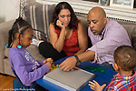 Family at home seven year old girl with father and stepmother playing strategy board game Blokus using colored tiles, 2 year old toddler brother looking on