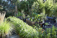 The small vegetable garden is located to one side of the terrace with raised beds enclosed by hazelnut frames