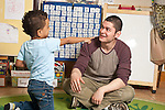 Education Preschool Headstart 3-4 year olds boy interacting with young male teacher