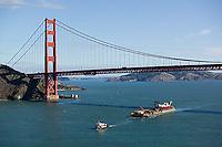 aerial photograph tug boat pulling loaded barge under the Golden Gate bridge, San Francisco, California