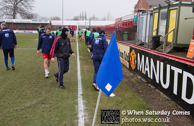 Altrincham 2 Worcester City 0, 23/03/2013. Moss Lane, Blue Square Bet North. The home team players wrapped up against the cold warming up before the Blue Square Bet North fixture between Altrincham and Worcester City at Moss Lane, Altrincham. The home team won the match 2-0 watched by 777 spectators on a day when most non-League football in England was cancelled due to adverse weather. Altrincham were historically one of the major English non-League teams but have never been promoted to the Football League. Photo by Colin McPherson.