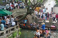 Suzhou, Jiangsu, China.  Tourists on Bridge Watch Boats with Tourists on Canal Rides in Tongli Ancient Town near Suzhou.