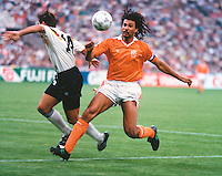 The Netherland's World Cup soccer team captain Rudd Gullit plays the ball past Germany's Thomas Berthold in World Cup Italia 90 action