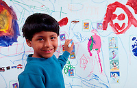 A smiling young Latino boy draws with markers on a large piece of mural paper.