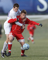 Amherst forward Christopher Martin (13) and St. Lawrence defender Austin Roney (20) battle for the ball.  NCAA Division III Sectionals. In double-overtime, Amherst College (white) defeated St. Lawrence University (red), 2-1, on Hitchcock Field at Amherst College on November 23, 2013.