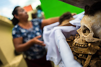 """A Mayan woman carries a wooden crate with a dried-up scull and bones of her deceased family member during the bone cleansing ritual at the cemetery in Pomuch, Mexico, 27 October 2019. Every year on the Day of the Dead, people of Pomuch, a small Mayan community in the south of Mexico, visit the cemetery to take part in a pre-Hispanic tradition of cleaning of bones of their departed relatives (""""Limpia de huesos""""). People who die in Pomuch are firstly buried for three years in an above-ground tomb then the dried-up bodies are taken out, bones are separated, wrapped in a decorated cloth, put into a wooden crate, and placed on display among flowers for veneration."""