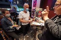 """Clubbesuch mit PCR-Test in Berlin.<br /> Am Wochenende vom 6. bis 8. August fand in Berlin das Pilotprojekt """"Clubculture Reboot"""" fuer eine moegliche Wiedereroeffnung der Clubs in der Hauptstadt statt. In einem von der Charite begleiteten Versuch durften an dem Wochenende bis zu 2000 Menschen in acht teilnehmenden Clubs ohne Maske und die ueblichen Coronaregeln feiern und tanzen. Eintrittskarten dafuer konnten nur personalisiert erworben werden und die Partygaeste mussten zuvor einen PCR-Test gemacht haben und zu weiteren Nachtestungen bereit sein.<br /> Das Projekt unter wissenschaftlicher Begleitung der Charite soll laut Senatskulturverwaltung aufzeigen, ob und wie Tanzveranstaltungen in Clubs """"auch unter pandemischen Bedingungen in Zukunft sicher moeglich sein koennen"""".<br /> Im Bild: Partygaeste warten am Samstagabend vor dem Berliner Club SO36 um an der legendaeren 80er-Jahre Party """"Dancing with Tears in your Eyes"""" teilzunehmen. Ihre personalisierten Tickets werden gescannt und mit dem Personalausweis verglichen.<br /> 6.8.2021, Berlin<br /> Copyright: Christian-Ditsch.de<br /> 7.8.2021, Berlin<br /> Copyright: Christian-Ditsch.de"""