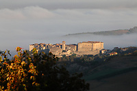 Alviano: A view of the historical center in a fall early morning, at the sunrise, when the old building are just enlightened, against the background of the fog that covers the valley of the Tevere river (Tiber river). The photo is taken from the citadel of the near old town of Lugnano in Teverina.