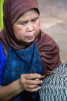 Yogyakarta, Java, Indonesia.  Woman Applying Wax to Design on Batik Cloth.