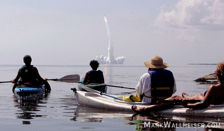 Mike Mahan (L), owner of Day Away Kayak Tours in Titusville, Florida, leads a group of 14 kayaks to Mosquito Lagoon in the Merritt Island Wildlife Refuge to watch the space shuttle Discovery lifts off the launch pad at Kennedy Space Center July 26, 2005.