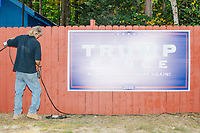 A worker picks up audio cables and equipment near a large Trump/Pence campaign sign after Donald Trump, Jr., son of president Donald Trump and a rising Republican political star, spoke at an outdoor campaign rally at The Lobster Trap in North Conway, New Hampshire, on Thu., Sept. 24, 2020.