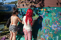 Two girls working on a collective group art piece, Hempfest Seattle, WA, USA.