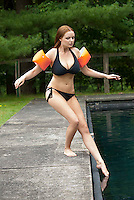 Woman wearing water wings. testing water with foot