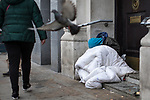 © Joel Goodman - 07973 332324 . 06/04/2017 . Manchester , UK . A person slumps against a wall in a doorway , wrapped in a duvet , in Piccadilly Gardens . An epidemic of abuse of the drug spice by some of Manchester's homeless population , in plain sight , is causing users to experience psychosis and a zombie-like state and is daily being witnessed in the Piccadilly Gardens area of Manchester , drawing large resource from paramedic services in the city centre . Photo credit : Joel Goodman
