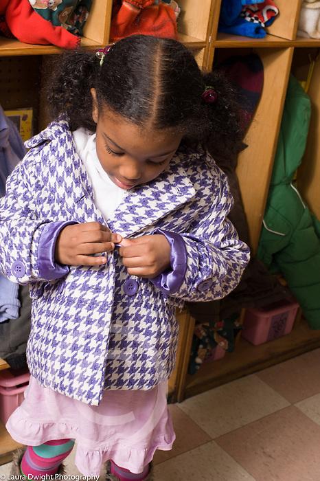 Education Preschool 3-4 year olds fine motor skills girl buttoning coat vertical