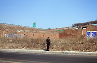 China. Jilin Province. A man standing by the side of the road in the town of Yanji, close to the border with North Korea. The town is part of the Korean Autonomous Prefecture in the north-east of the country. 2011