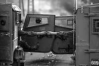 Ramallah, West Bank. Israeli soldiers in armoured vehicles share a cup of coffee in the midst of clashes with Palestinian youths. Less than ten minutes later the soldiers found themselves in a gun battle with militants.