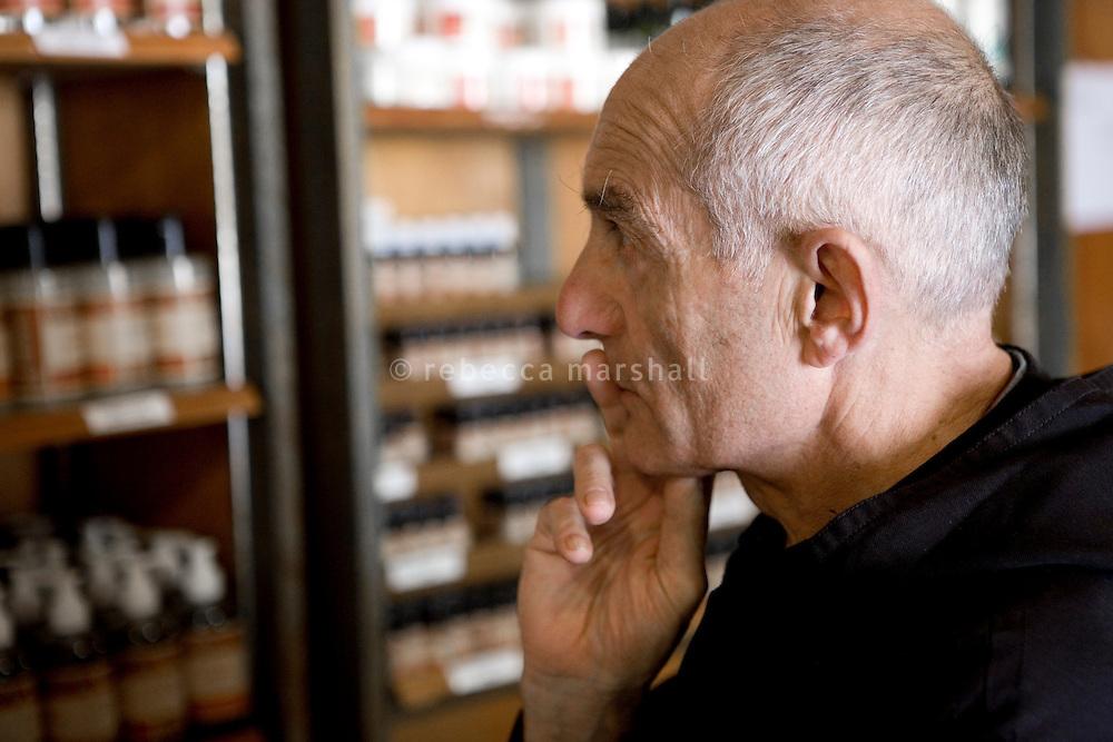 Frere Raymond surveys displays of perfume in the abbey shop, Ganagobie Monastery, Alpes de Haute Provence, France, 17 July 2009.