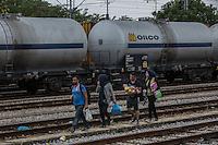 gruppo di migranti camminano lungo la ferrovia con un neonato in braccio   migrant group walking along the railroad tracks with a baby