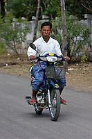 Myanmar, Burma, near Bagan.  Burmese Man Riding Motor Bike.