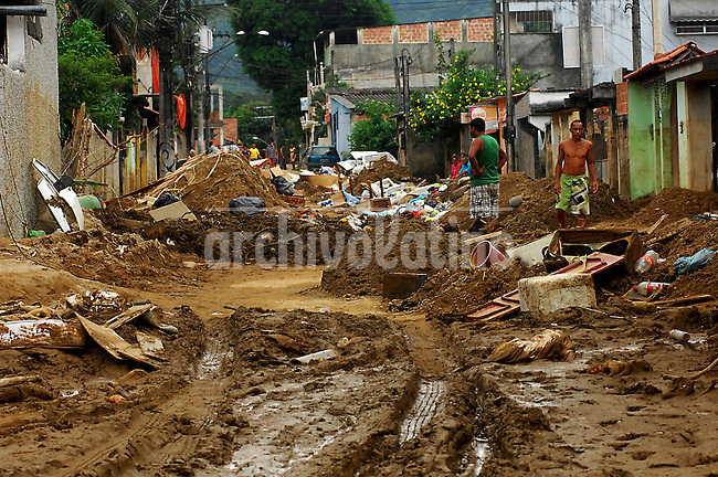 People walk along a road in a devastated area after recent mudslides at Xerem neighbourhood, in Duque de Caxias, some 50 km north of Rio de Janeiro, Brazil, January 9, 2013. (Austral Foto/Stringer)