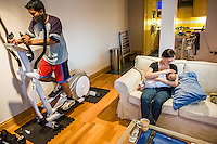 A young mother breastfeeds her baby in her living room while her husband works out on his excercise machine.<br /> <br /> 15/05/2012<br /> Hampshire, England, UK