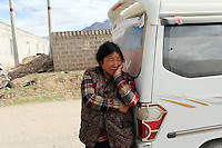A Tibetan woman leans against a car in Zaduo, in the far interior of the Tibetan Plateau, in western China. Relocation communities been created to house nomadic herders moved from the highland grasslands. The nomads have been blamed for contributing to the deterioration of the grasslands, so have been moved, sometimes forcibly, into newly built towns that can be found across the plateau.