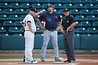 Bowling Green Hot Rods manager Jeff Smith (40) meets with Winston-Salem Dash manager Ryan Newman (5) and umpires Rainiero Valero and Zee Zdenek prior to the game at Truist Stadium on September 7, 2021 in Winston-Salem, North Carolina. (Brian Westerholt/Four Seam Images)