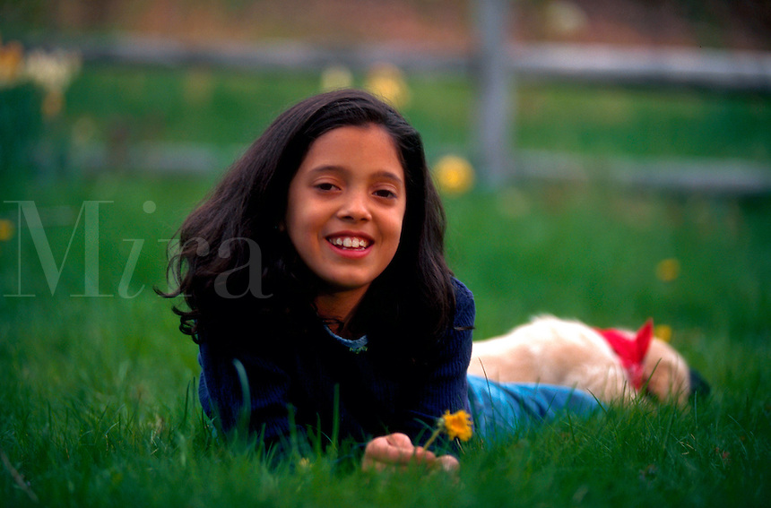 Portrait of smiling ten year old girl lying in the grass.