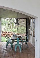Sliding windows open from the rustic kitchen/dining area into the garden which features a pile of logs