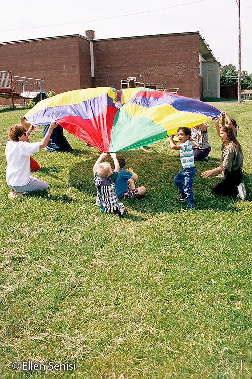 MR / Schenectady, NY.Yates Arts Magnet School / Special Education Class.Students, aides, teacher lift parachute on playground for lesson on motor coordination & cooperation..MR: JK.PN#: 21125                       FC#: 21658-00802.scan from slide.©Ellen B. Senisi