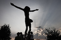 The bronze sculpture of the Risen Christ. With a tear-like liquid dripping from two knees, the Risen Christ has been a mystery in Medjugorje since 2001.  Faithful get in line and,  sweeping their handkerchiefs on the Christ Knees,  collect  the liquid.<br /> Medjugorje, Bosnia and Herzegovina. July 2012