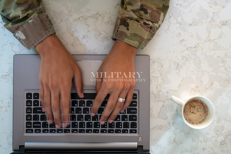 US Army man at home on computer stock photo DOD complient rights managed model released