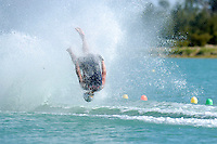 A barefoot waterskier falls during a jump competition