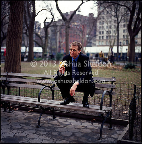 Man in suit sitting on top of park bench holding a banana<br />