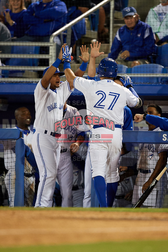 Dunedin Blue Jays Connor Panas (27) high fives teammates, including Deiferson Barreto (left) after hitting a home run in the bottom of the sixth inning during a game against the Clearwater Threshers on April 8, 2017 at Florida Auto Exchange Stadium in Dunedin, Florida.  Dunedin defeated Clearwater 12-6.  (Mike Janes/Four Seam Images)